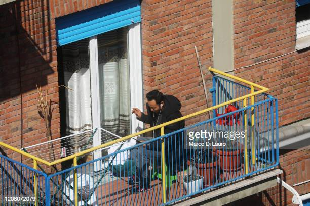 A man plays with his son and cell phone while smoking a cigarette on his balcony during lockdown on March 23 2020 in Rome Italy As Italy extends its...