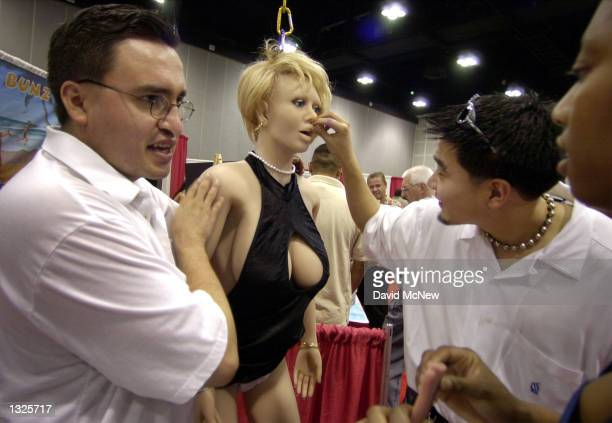 A man plays with the mouth of a ''Super Babe'' sex doll made of pure silicone over an aluminum skeleton at the fifth annual Erotica LA adult...