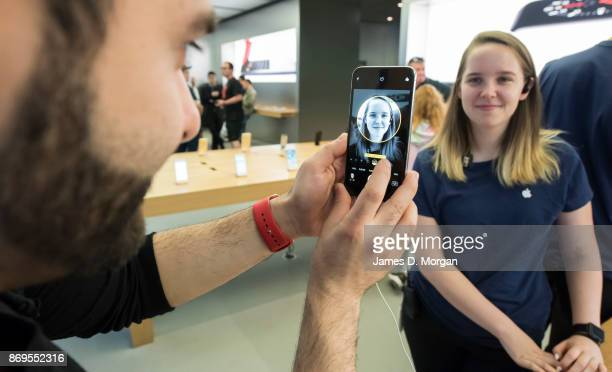 A man plays with the new IPhone X at the Apple Store on November 3 2017 in Sydney Australia Apple's latest iPhone features face recognition...