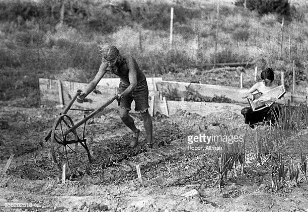 A man plows his field while a woman plays an autoharp circa July 1969 in New Mexico
