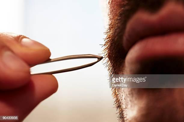 Man plucking beard