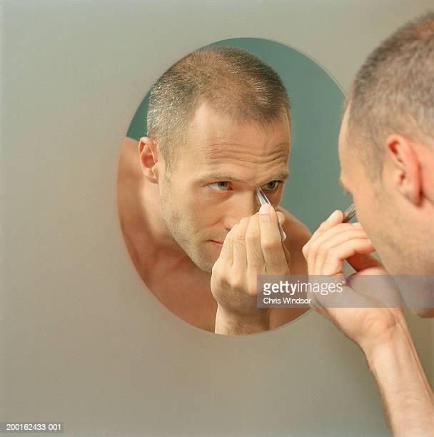 Man plucking eyebrows, reflection in mirror