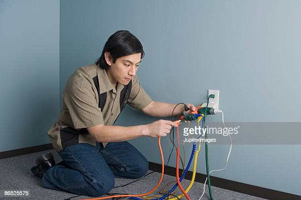 Man plugging computer wires into outlet