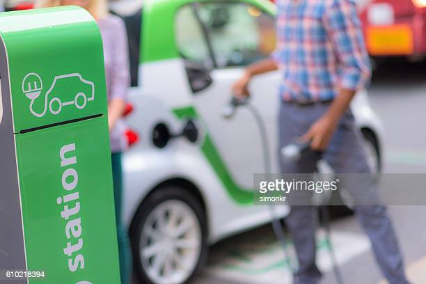 Man plugging Smart electric car by charging station in city