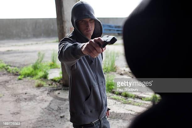 Man point gun at rival