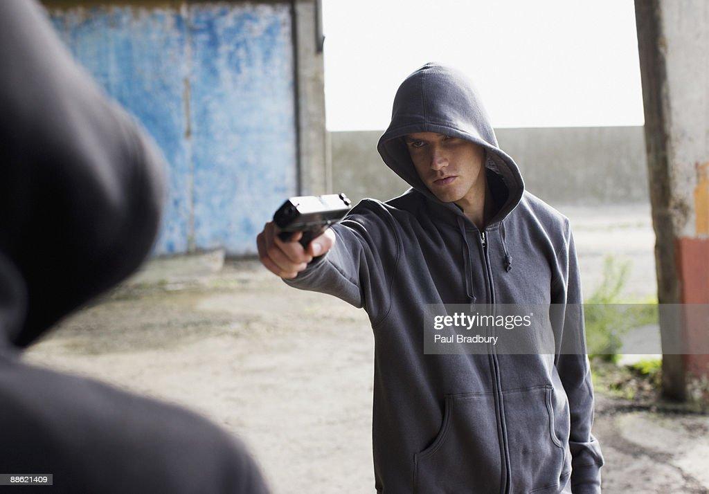 Man point gun at rival : Stock Photo