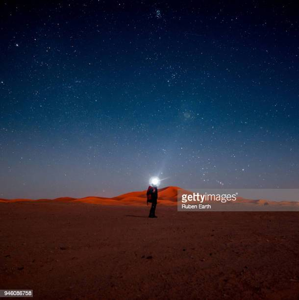 man point the head light to the night sky with starts in the sahara desert - merzouga stock pictures, royalty-free photos & images
