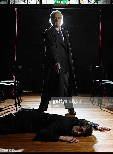 man pointing a gun at a dead body - dead gangster stock pictures, royalty-free photos & images