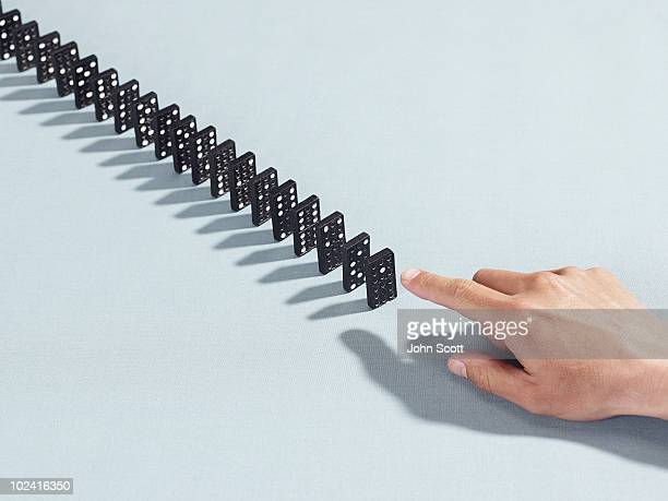 man pointing at a row of dominoes - repetition stock pictures, royalty-free photos & images