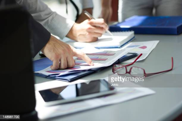 Man pointing at a statistic paper in a business meeting