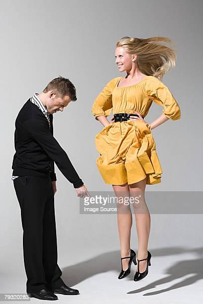 A man pointing at a woman jumping