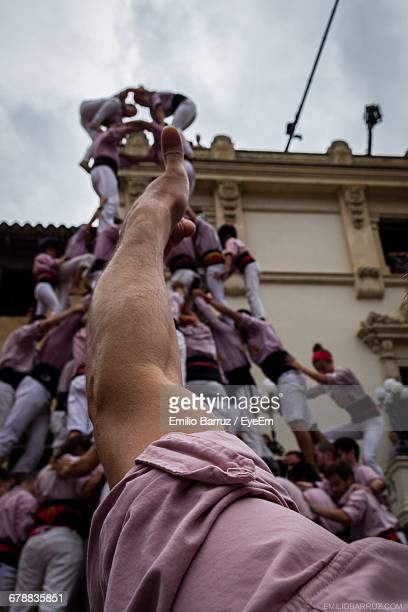 man pointing at human tower at festival - human pyramid stock photos and pictures
