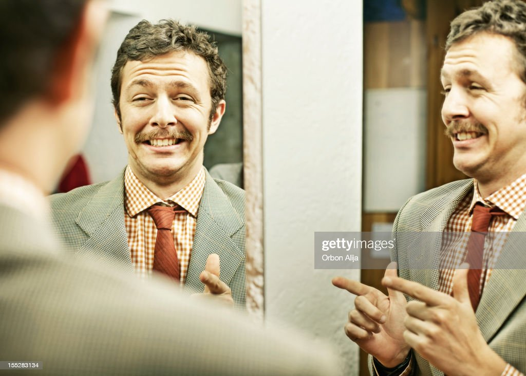 Man pointing at reflection in mirror : Stock Photo
