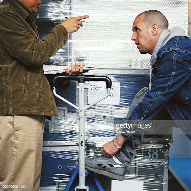 Man pointing finger at workman tying shoe lace, side view