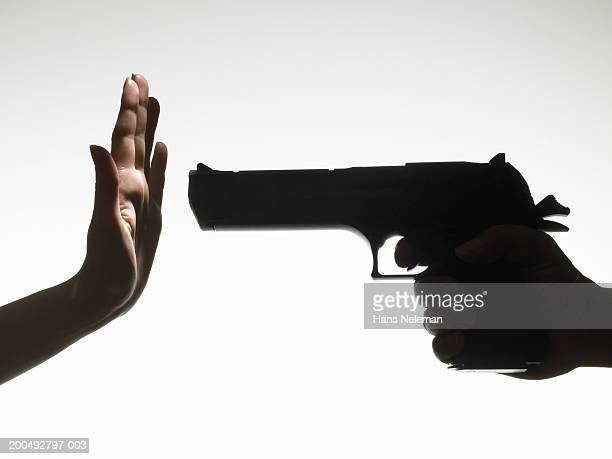 Man pointing gun at woman making stop gesture with hand, close-up