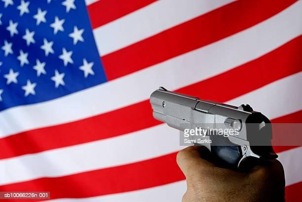 Man pointing gun on American flag
