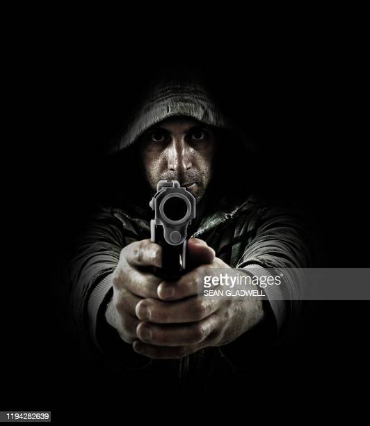 man pointing gun on black background - terrorism stock pictures, royalty-free photos & images