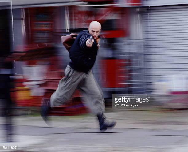 Man pointing gun, while running