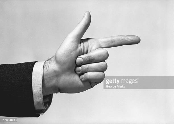 Man pointing in studio, close-up of hand, (B&W)