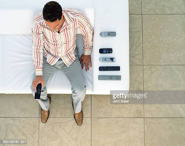 man pointing remote control handset, elevated view - hand on knee stock pictures, royalty-free photos & images