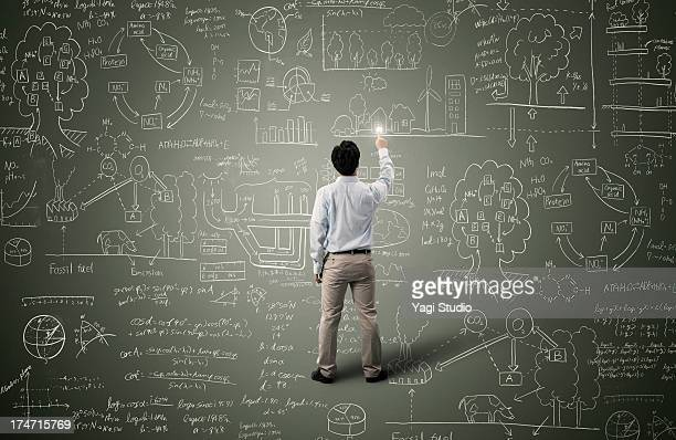 Man pointing to formula and picture on blackboard