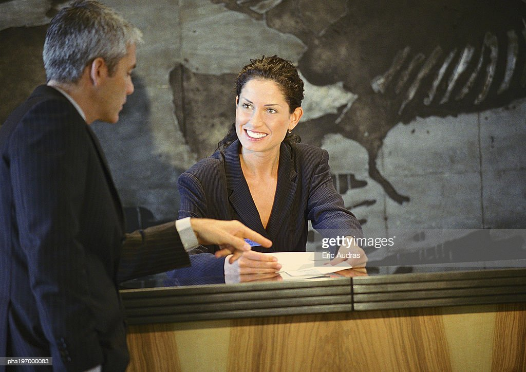 Man pointing to paper in woman's hands : Foto de stock