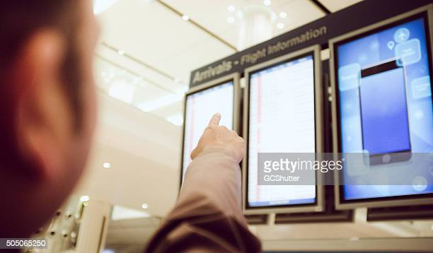 man pointing towards aiport display panel in a arrival hall - tall high stock pictures, royalty-free photos & images