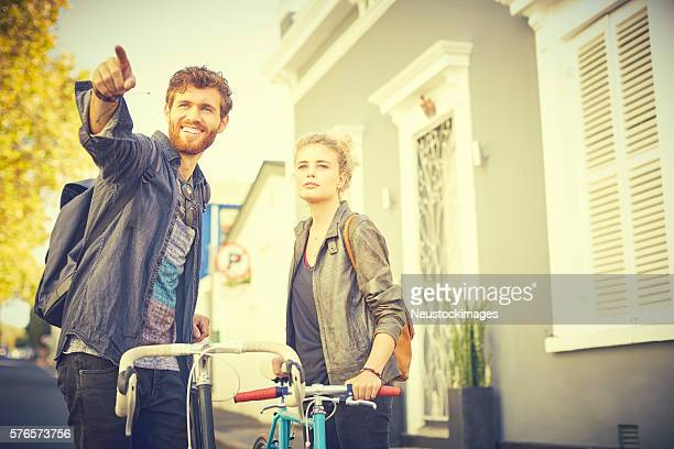 Man pointing while standing by woman and bicycles