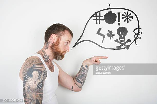 Man pointing with speaking bubble signs on wall