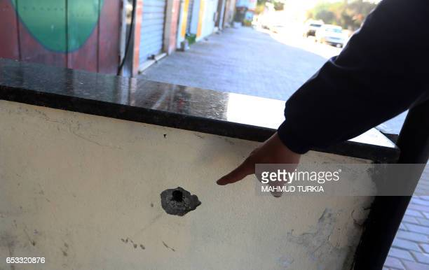 A man points a bullet hole in the Hay alAndalus neighbourhood of the Libyan capital Tripoli on March 14 following clashes between rival armed groups...
