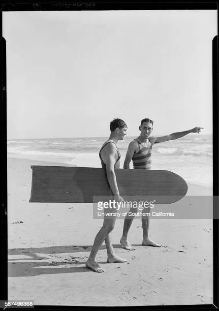 Man points a surfer towards the waves at Hollywood by the Sea, Oxnard, CA, 1927.