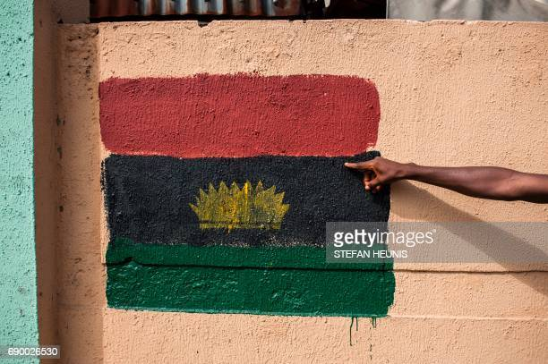 A man points at a Biafran flag painted on a wall on Old Market road in Onitsha on May 30 during a shutdown in commemoration of the 50th anniversary...