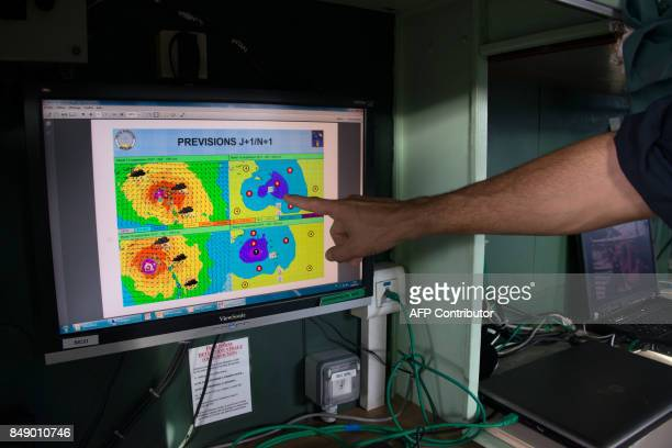 A man points at a screen monitoring the weather and the progression of Hurricane Maria onboard the French marine frigate Germinal which arrived at...