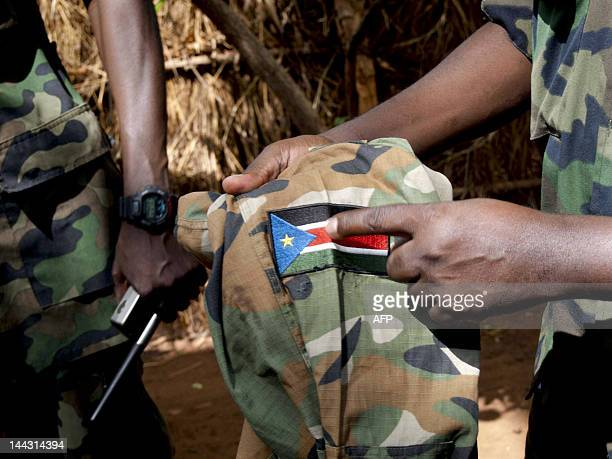 Man points at a Sudanese Peoples Liberation Army uniform which was found with Ceasar Acellam, a senior member of the Lord's Resistance Army, at the...