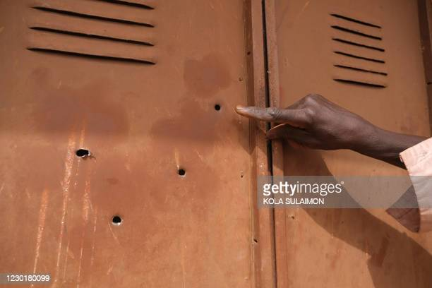 Man points at biullet holes at the Government Science Secondary school in Kankara, in northwestern Katsina State, Nigeria on December 16, 2020. -...