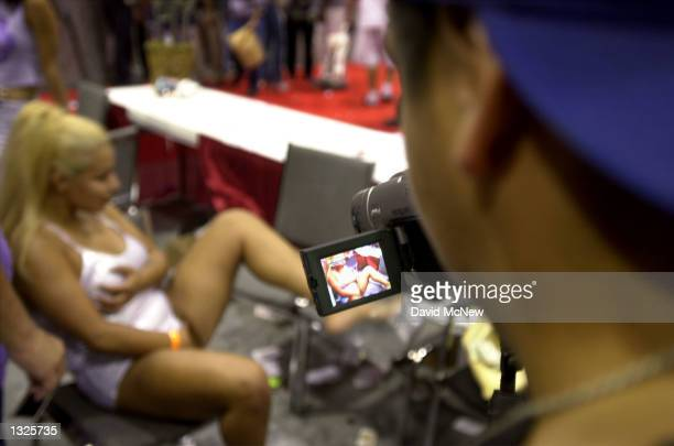 A man points his video camera at an exotic dancer at the fifth annual Erotica LA adult entertainment trade show July 14 2001 in Los Angeles CA The...