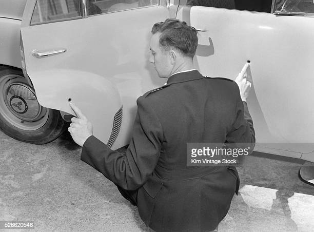 Man points out bullet holes in his car ca 1955