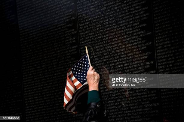 TOPSHOT A man points to a name while visiting the Vietnam War Memorial on Veterans Day November 10 2017 in Washington DC / AFP PHOTO / Brendan...