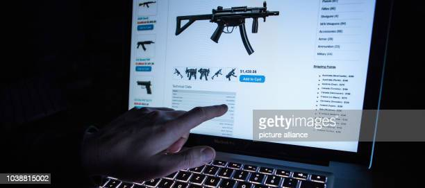 Man points to the webpage of an online shop that sells machine guns on the Darknet in Rottweil,Germany, 12 November 2016. Photo:Silas Stein/dpa  ...