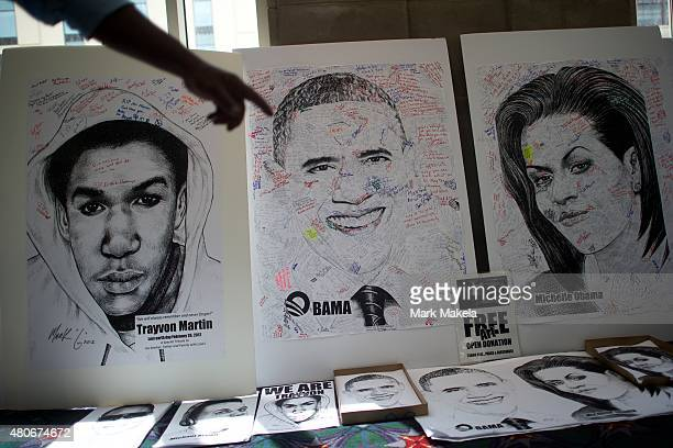 A man points towards autographed drawings of Trayvon Martin Barack and Michelle Obama at the 106th NAACP national convention on July 14 2015 in...
