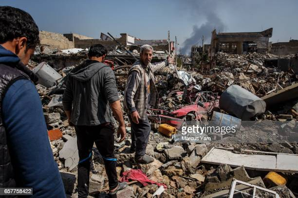 A man points towards the fighting as they walk through an area that was affected by a reported coalition air strike in the alJadida neighborhood of...