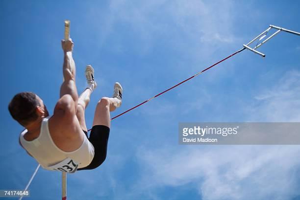 'Man pole vaulting, low angle view'