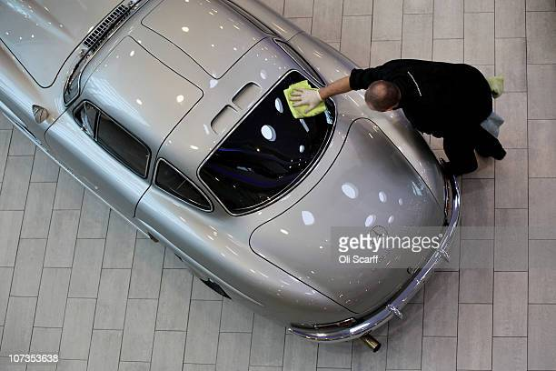 A man polishes a 1955 MercedesBenz 300SL Gullwing Coupe displayed in MercedesBenz World prior to its auction on December 6 2010 in Weybridge England...