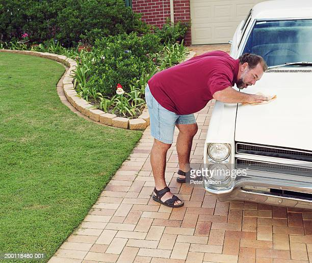 Man polishing car bonnet in driveway, elevated view