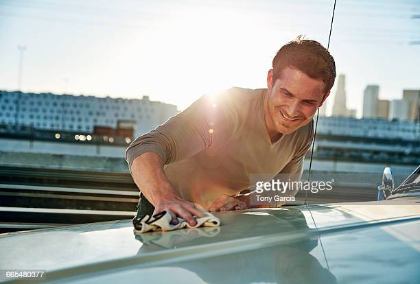 Man polishing car smiling, Los Angeles, California, USA