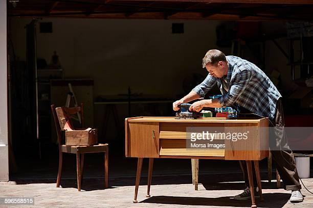 Man polishing furniture outside house