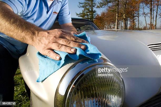 man polishing his classic car with cloth
