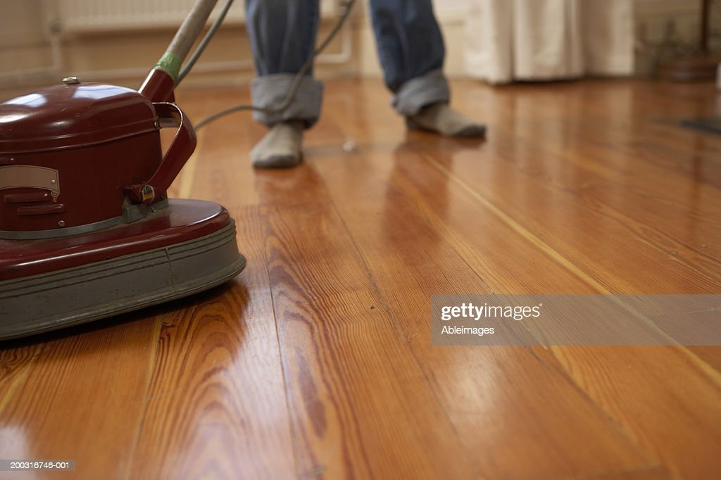 Man polishing wooden floor, low section : Stock Photo