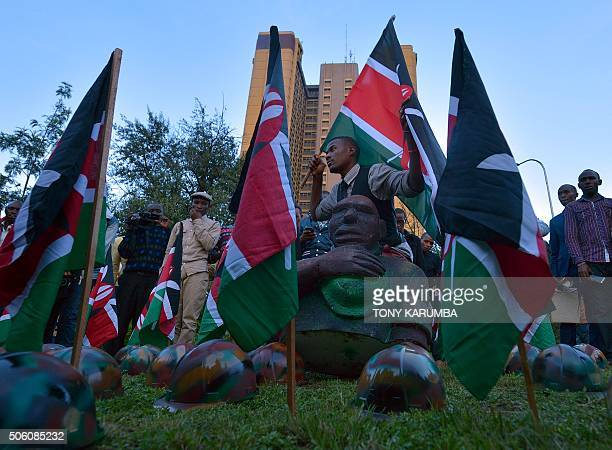 A man poses among symbolic helmets and flags at a vigil on January 21 2015 in Nairobi in honour of Kenya Defence Forces soldiers killed on an African...