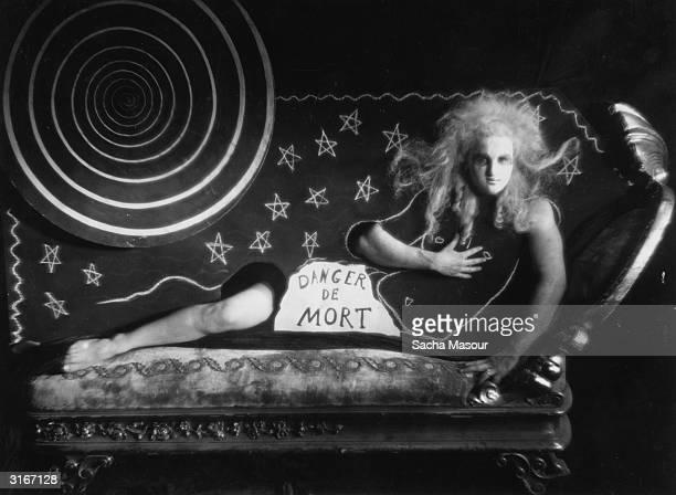 A man poses as a woman on a chaiselongue ina scene entitled 'Danger de Mort' from Jean Cocteau's film 'Le Sang d'un Poete'